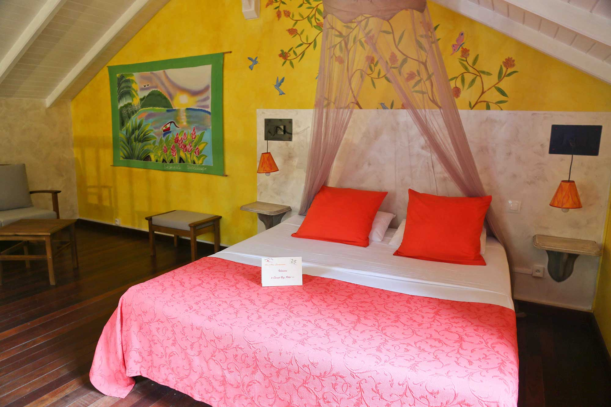yellow room and pink bed at the Caraïb'Bay Hôtel