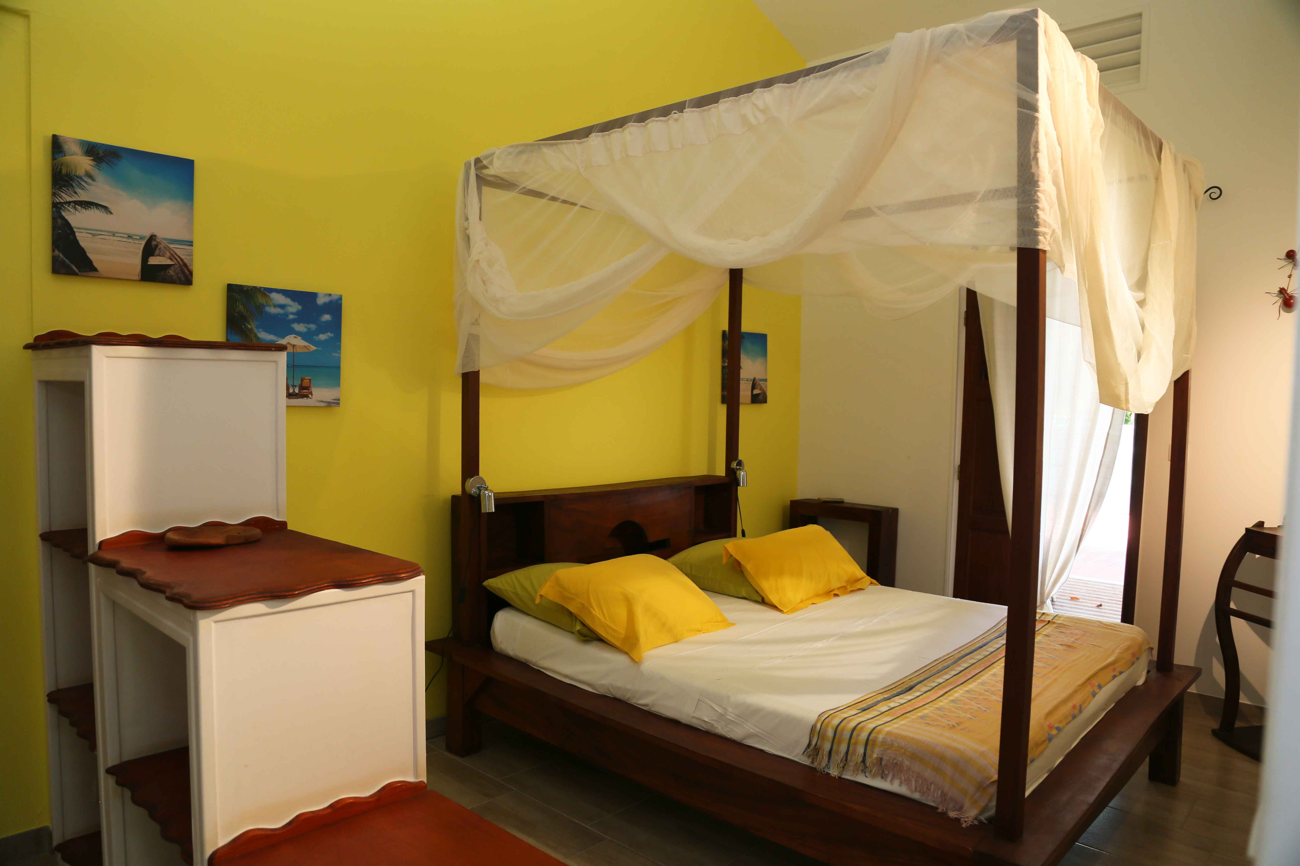 villa Kanouan's room with yellow walls and double bed